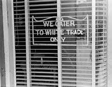 While the blatant racist signs of the 50s that proclaimed