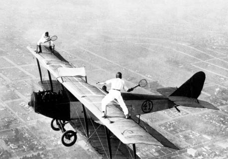 Stuntmen pretend to be playing tennis on an airplane in 1923. Would you like to be a stuntman?